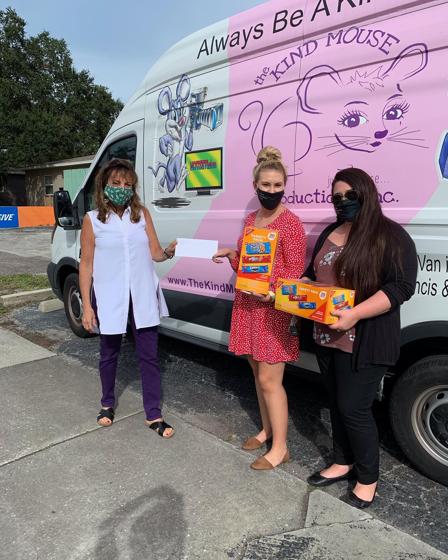 Three women in face masks stand in front of a pink and white van.