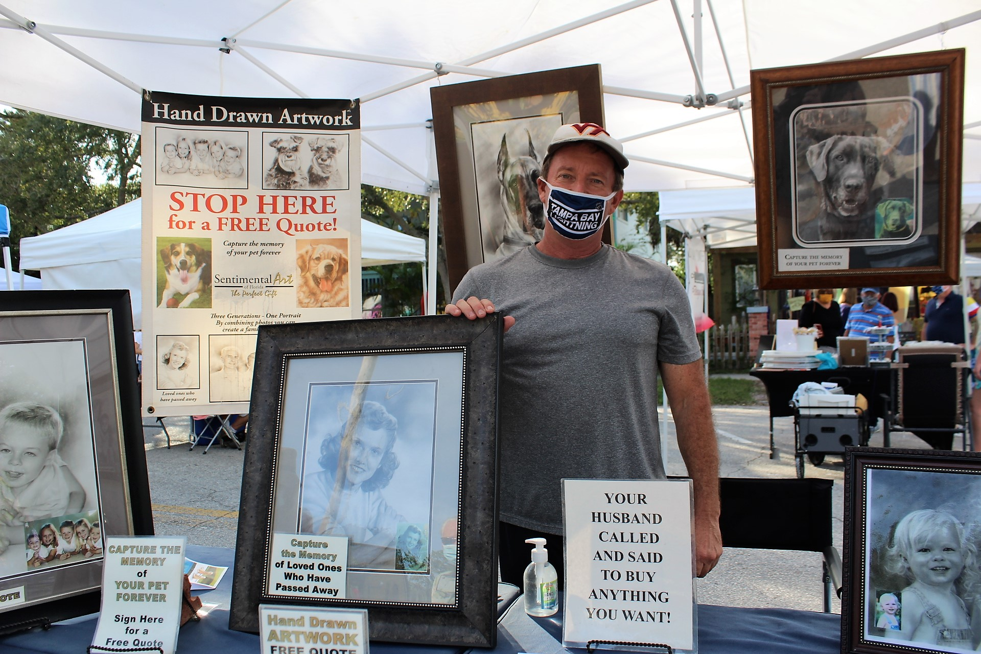 A man in a tent with a face mask standing with hand-drawn art in frames
