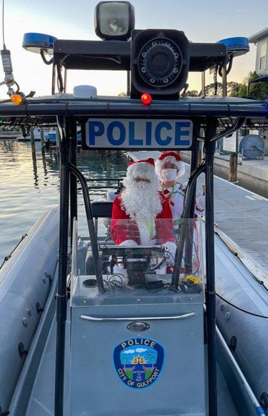 A man dresses as Santa and Mrs. Claus on a police boat in a marina at sunset.