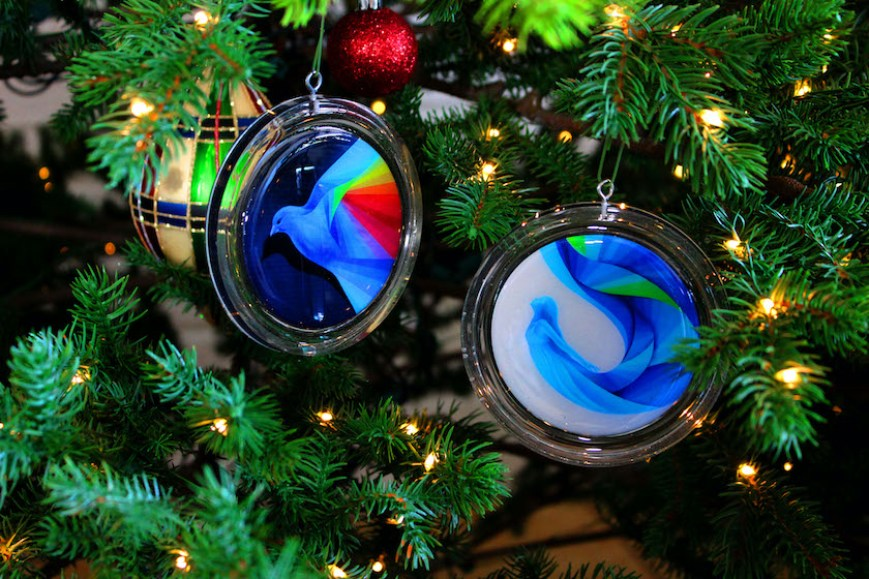 A close up photo of blue art ornaments on a tree.