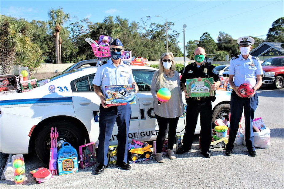 A group of people in face masks, and two in military/police uniforms, stand in front of a police cruiser outside surrounded by toys.