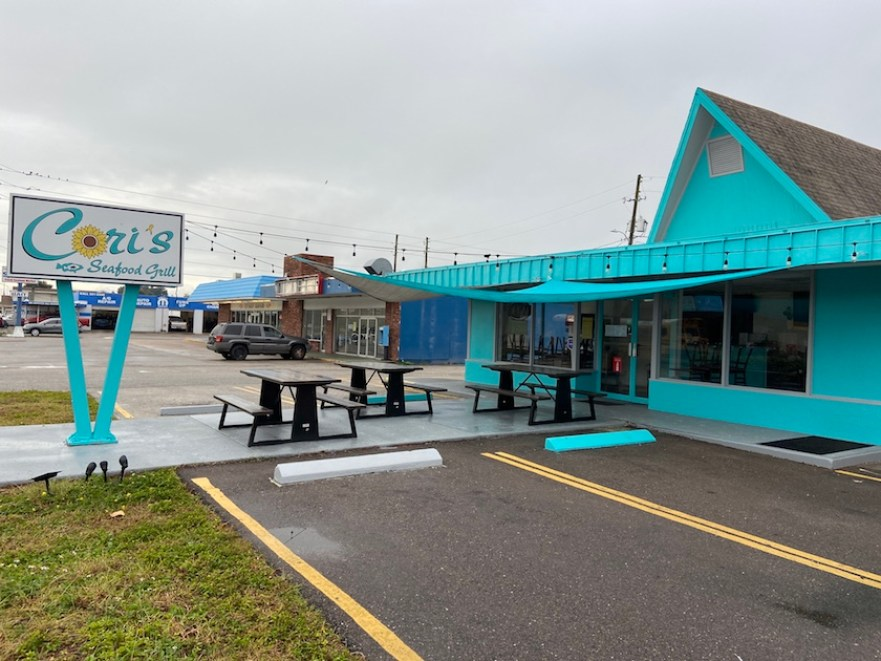 "A restaurant from the outside with picnic tables and bright blue paint and a sign that reads ""Cori's"""