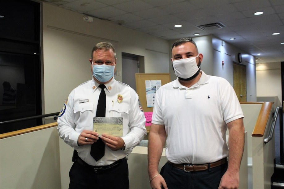 Two men in white shirts and face masks look at the camera.