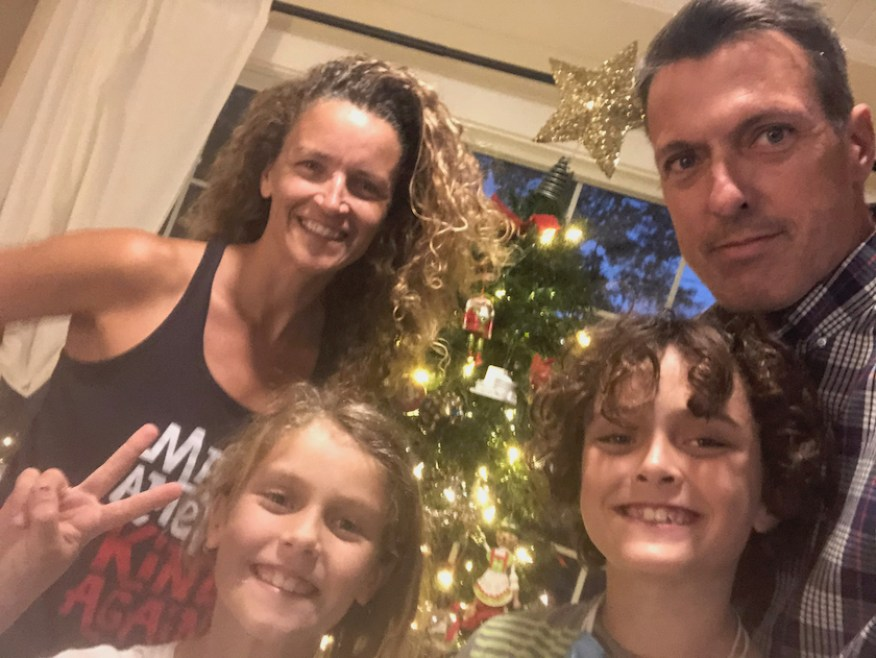 A family selfie photo in front of a Christmas tree.
