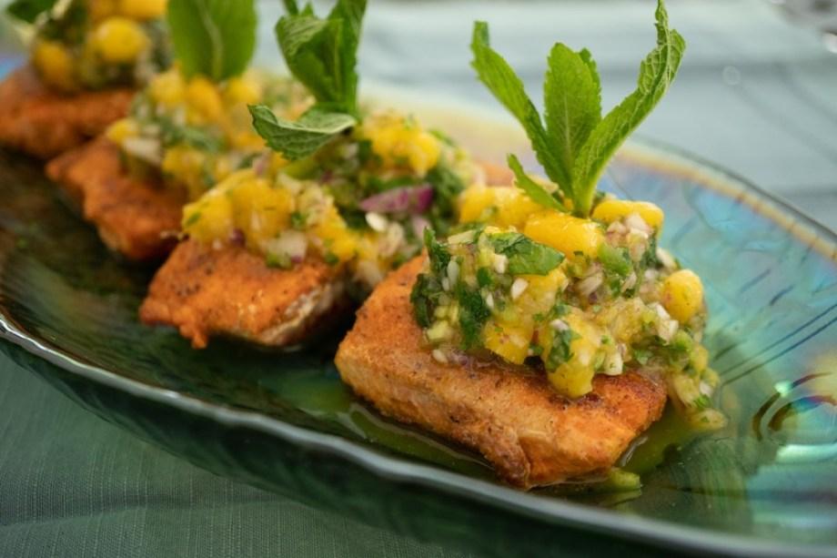 A closeup photo of salmon with mango salsa and green garnish.