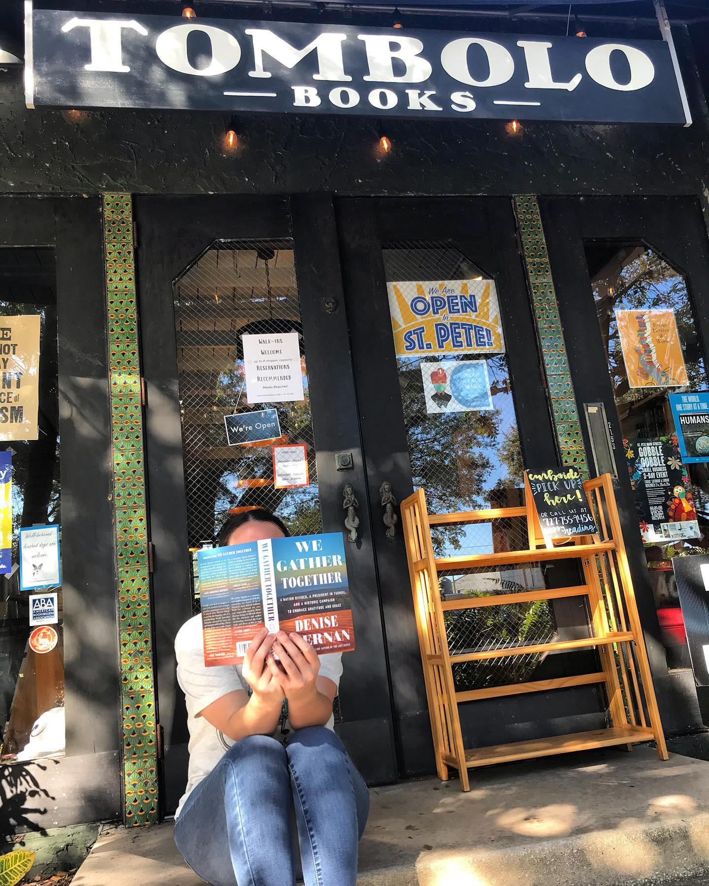 """A person outside a bookstore holding a book open over their face. Sogn reads """"Tombolo Books."""""""