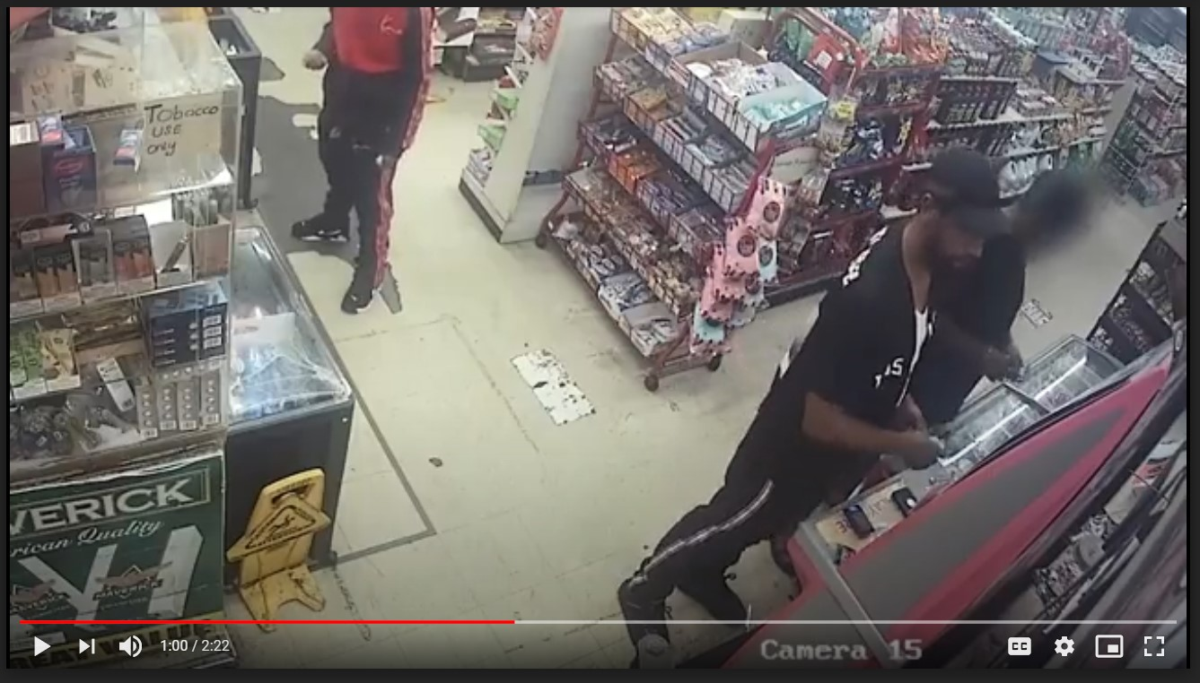 A video still of men at a counter in a convenience store.