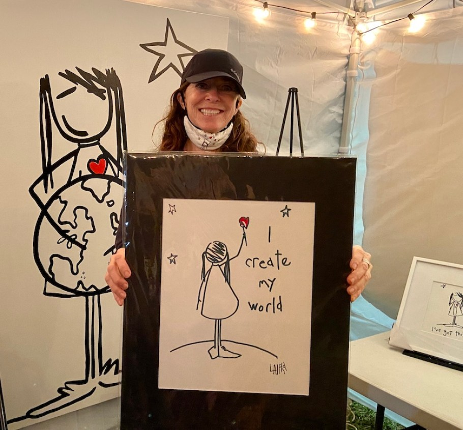 A woman in a black cap standing in a white tent with a framed drawing of a little girl