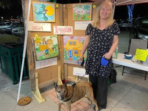 A woman standing with a dog on a leash in front of a wall of art