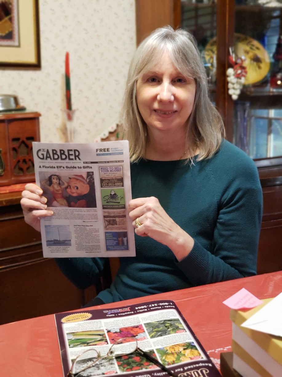 A woman at a table holding up a Gabber Newspaper.