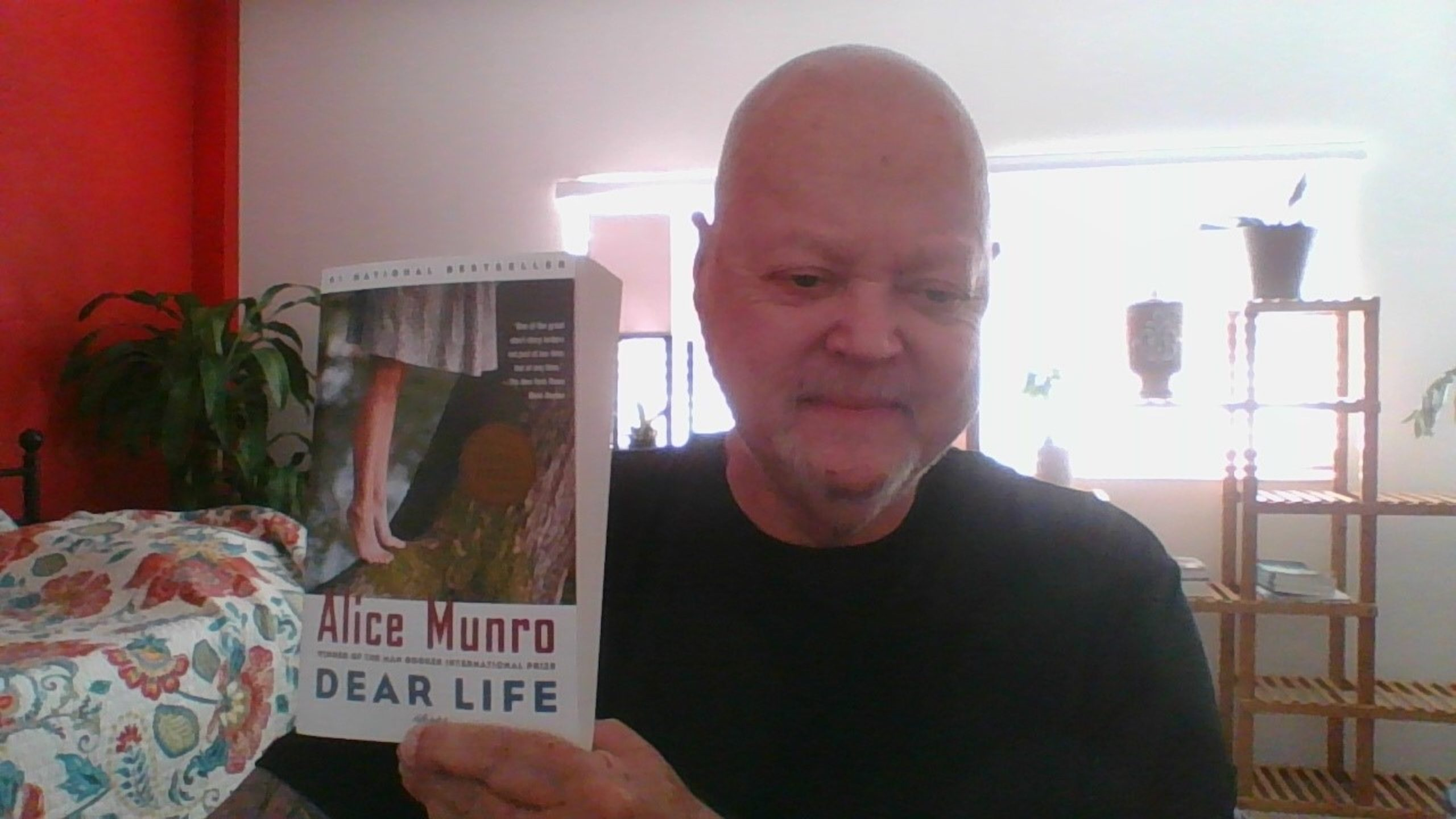 A man holding a book by Alice Munro