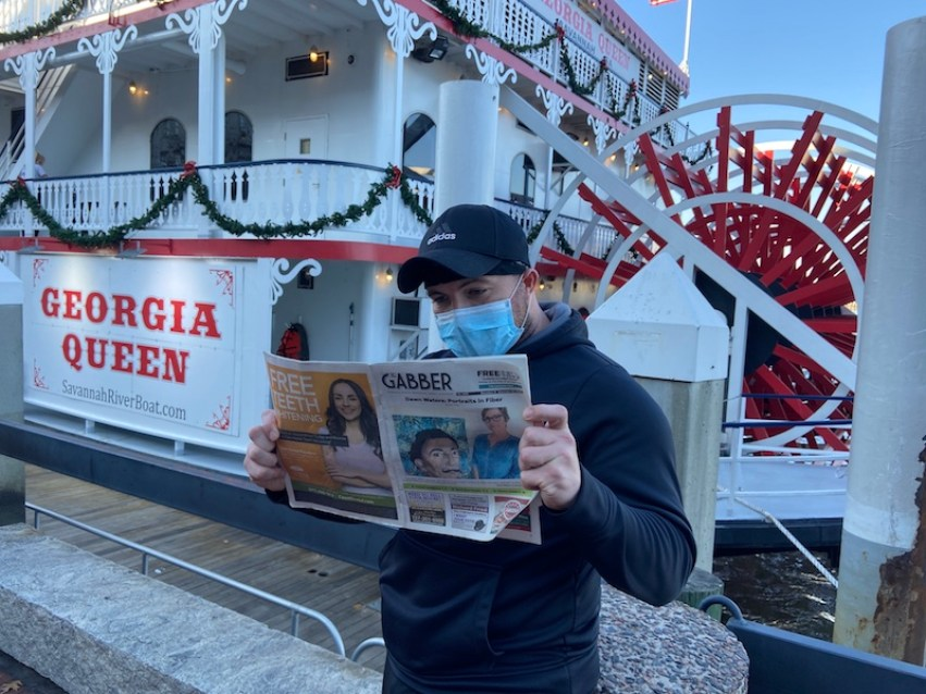 """A man with a Gabber Newspaper in front of a paddle boat with a sign that reads """"Georgia Queen"""""""