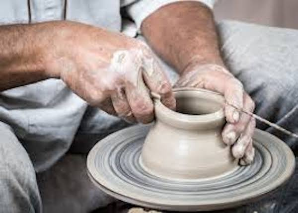 A man molding a clay pot