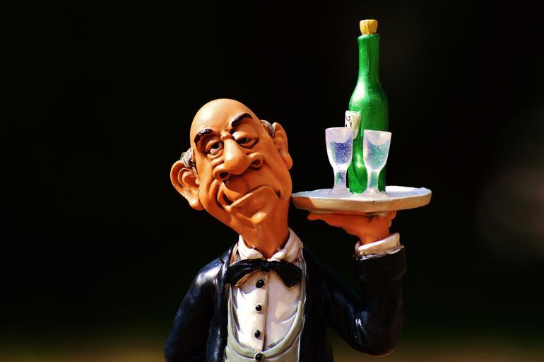 Clay molding of an old man with a tray filled with wine and wine glasses.