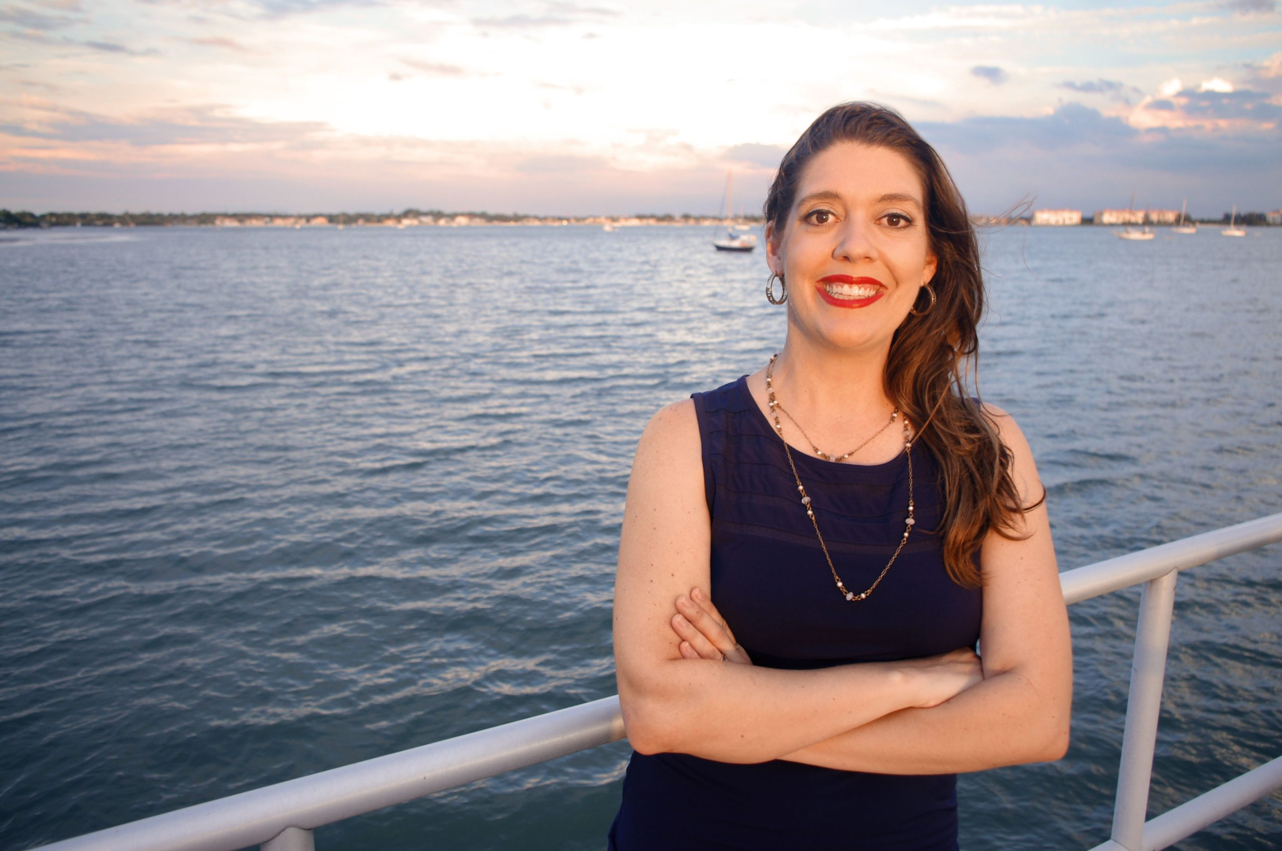 A woman in a dark, sleeveless shirt by the water at sunset.