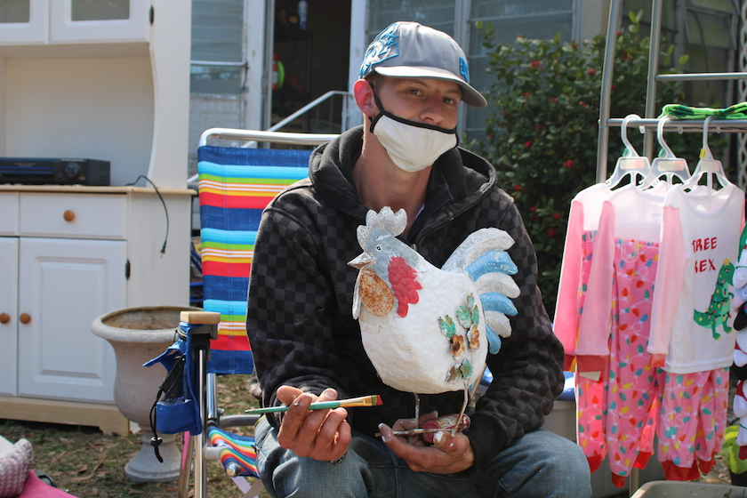 A man in a ball cap and face mask holding a tin chicken and a paintbrush.