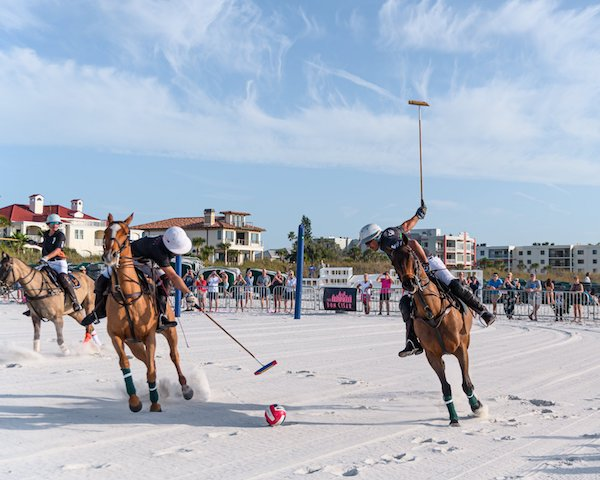Two horse riders playing a traditional game of horse polo on the beach