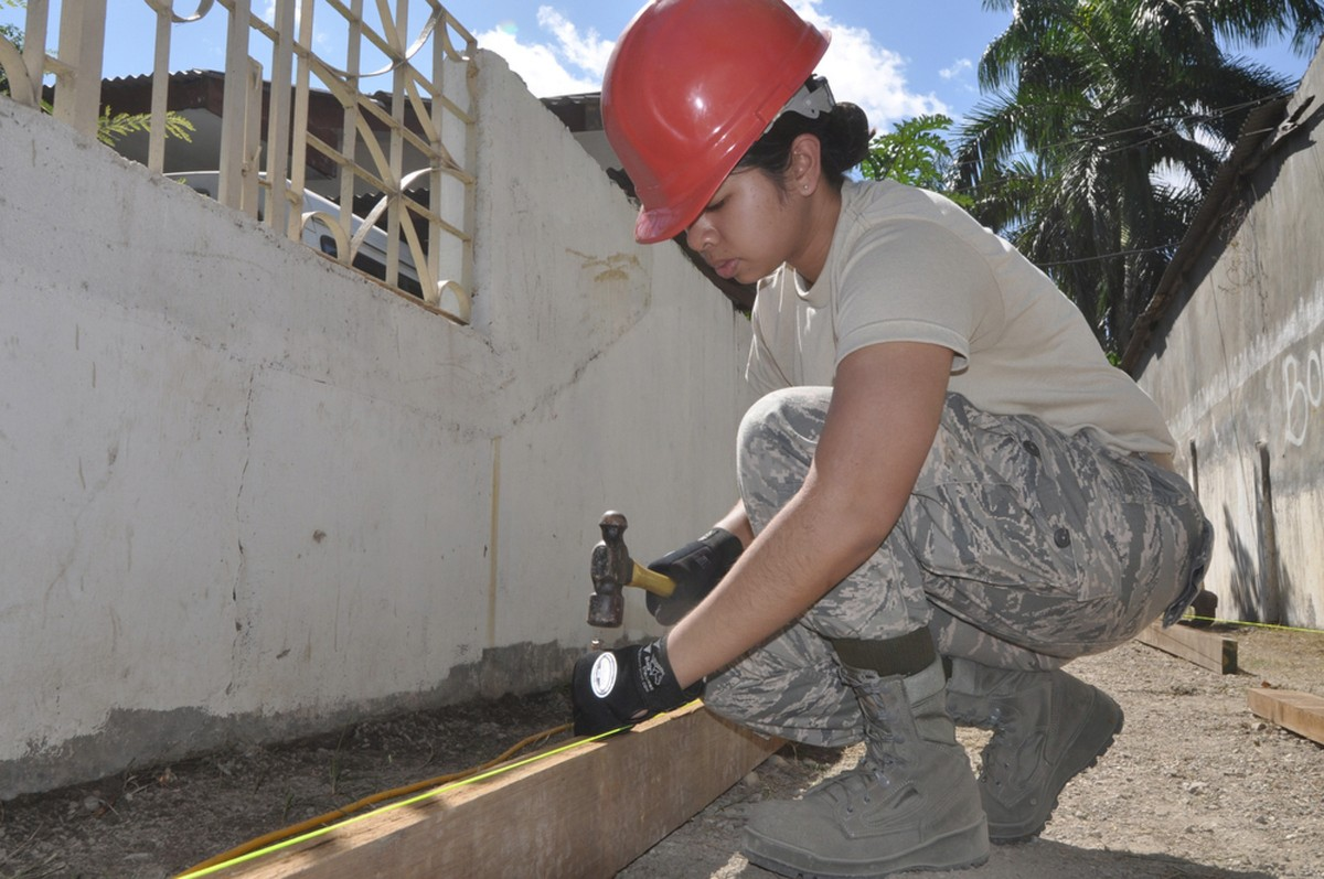 A female construction worker hammering a nail into a post.