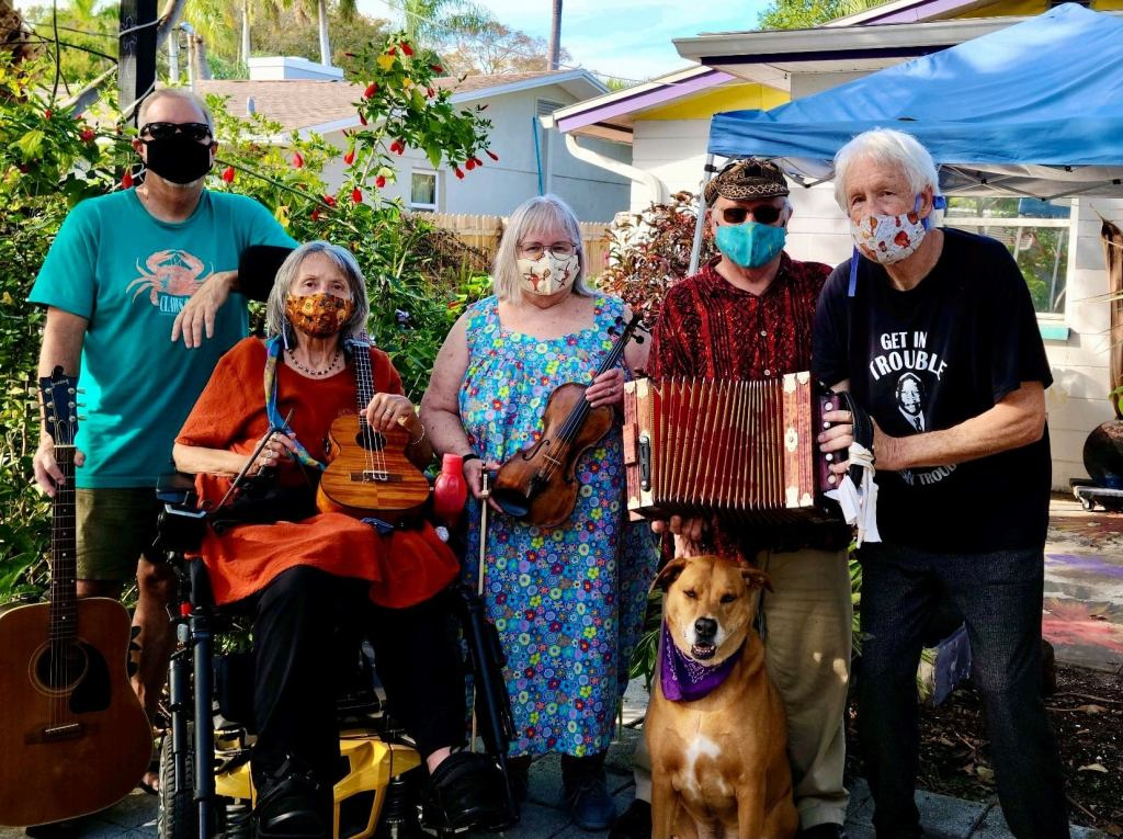 Five colorfully clad band members and a dog holding instruments in a backyard