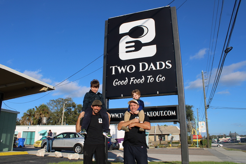"Two men with young boys on their shoulders stand in front of an outdoor sign that reads ""Two Dads Good Food to Go"""