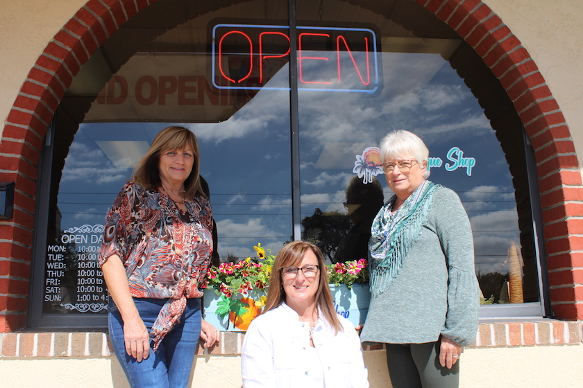 "Three woman standing and kneeling in front of a shopfront with a sign that says ""Open"""