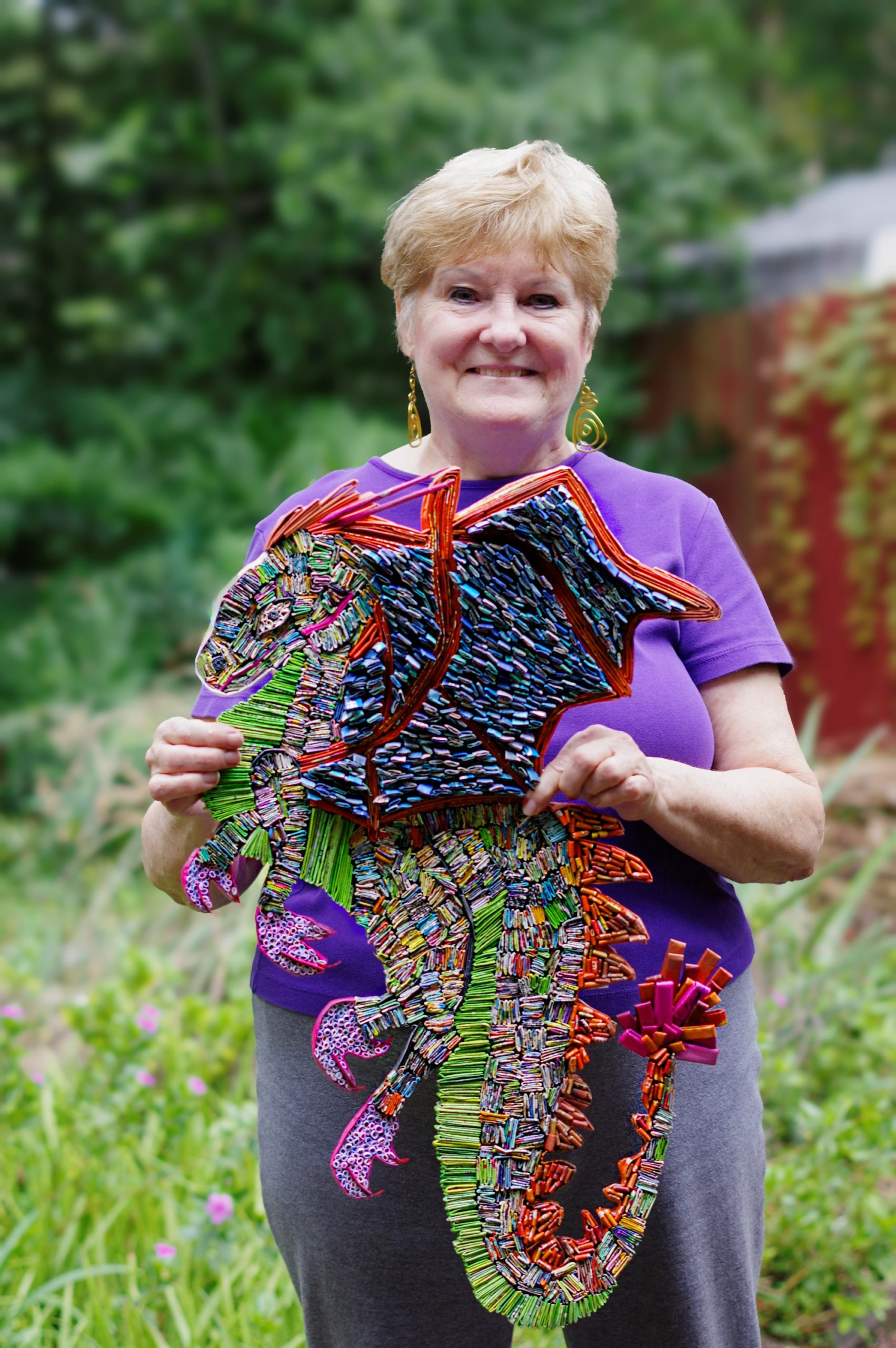 Donna Plunkett holding up a red and purple paper dragon.