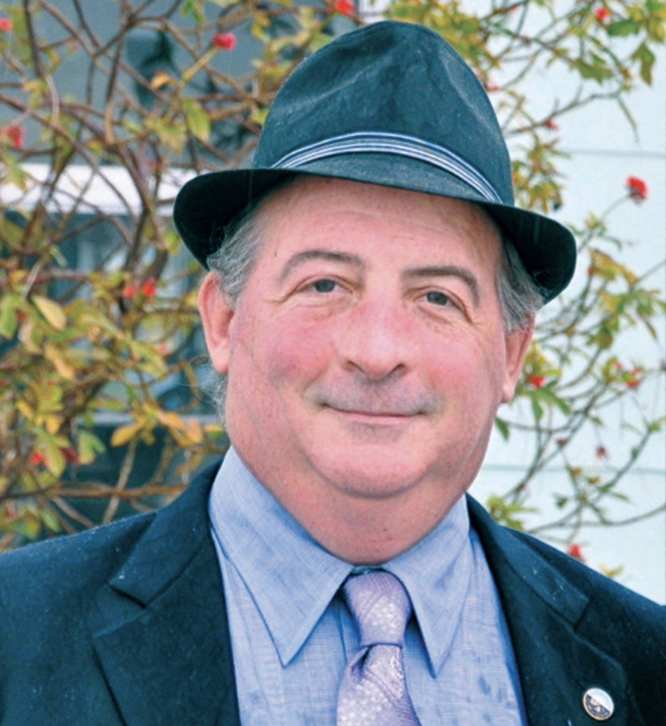 A headshot of a man in a suit, tie and fedora hat.