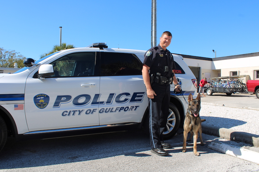 A photo of a male police officer with a German shepherd K-9 officer in front of a City of Gulfport Police SUV