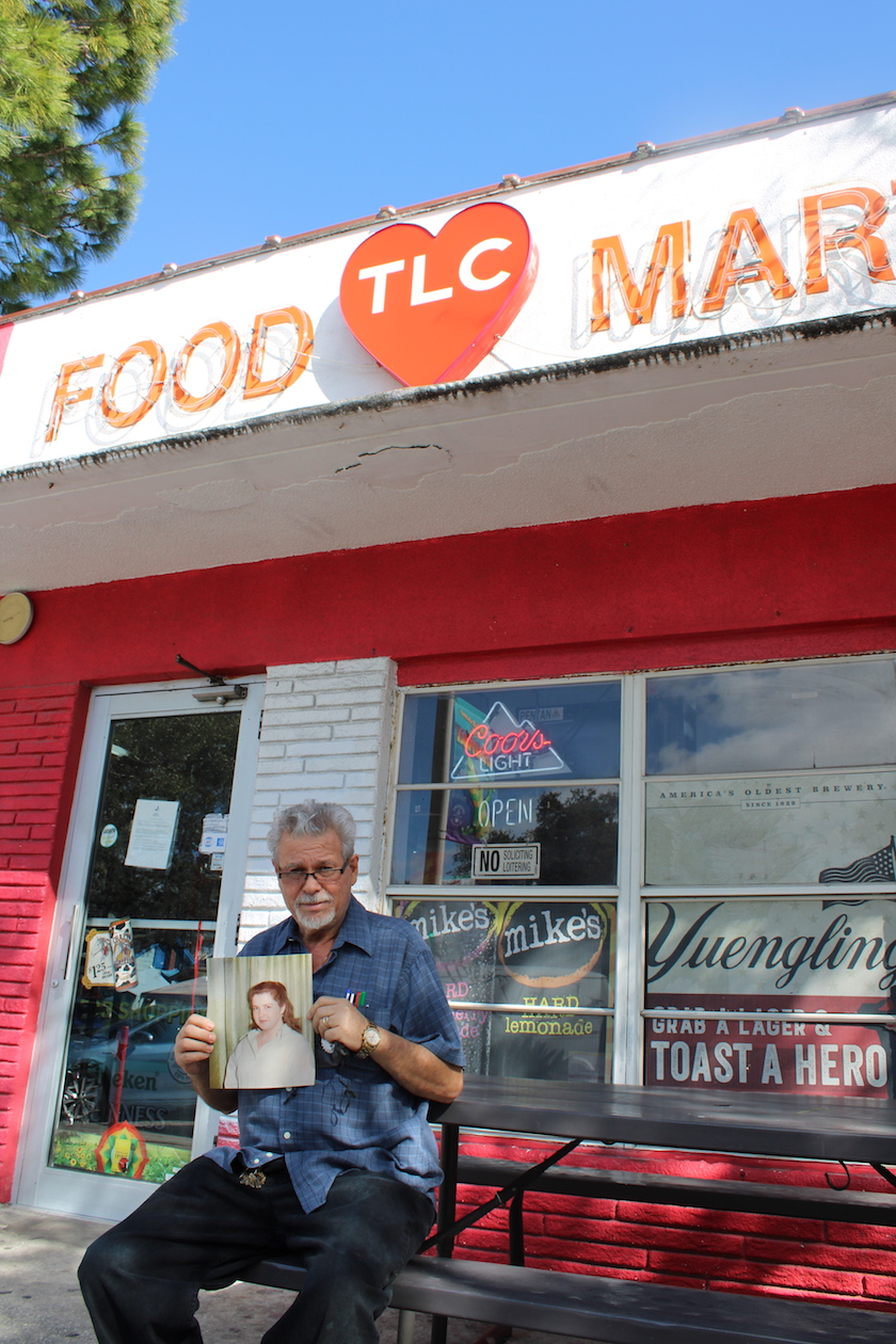 A man sitting outside a convenience store holding a photo of a woman.