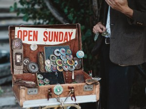 """Vintage suitcase with knickknacks spilling out that reads """"Open Sunday"""""""