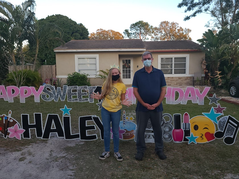 """A man and a young woman in face masks standing in front of a house with a sign that reads """"Happy Sweet 16 Birthday Haley"""""""
