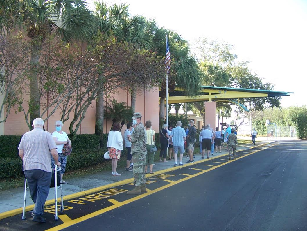 A line of people outside a recreation center.