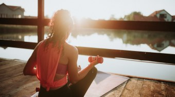 Woman in pink tank top working out by lake.