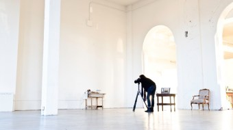 White gallery with a darkly-clad man shooting a photograph