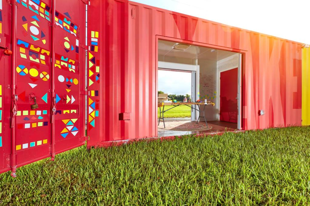 Red shipping container with a colorful mural painted on the side