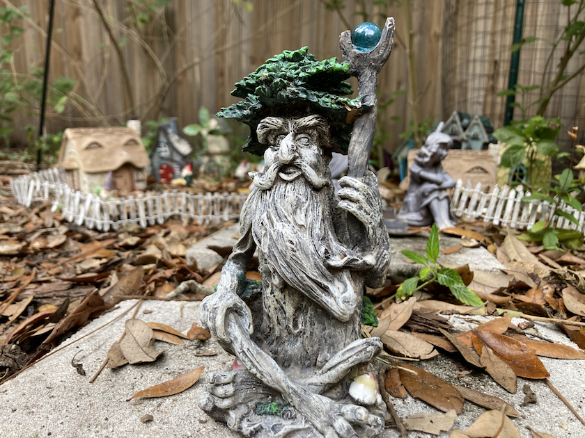 A photo of a garden gnome with green hair , a long beard and a staff.