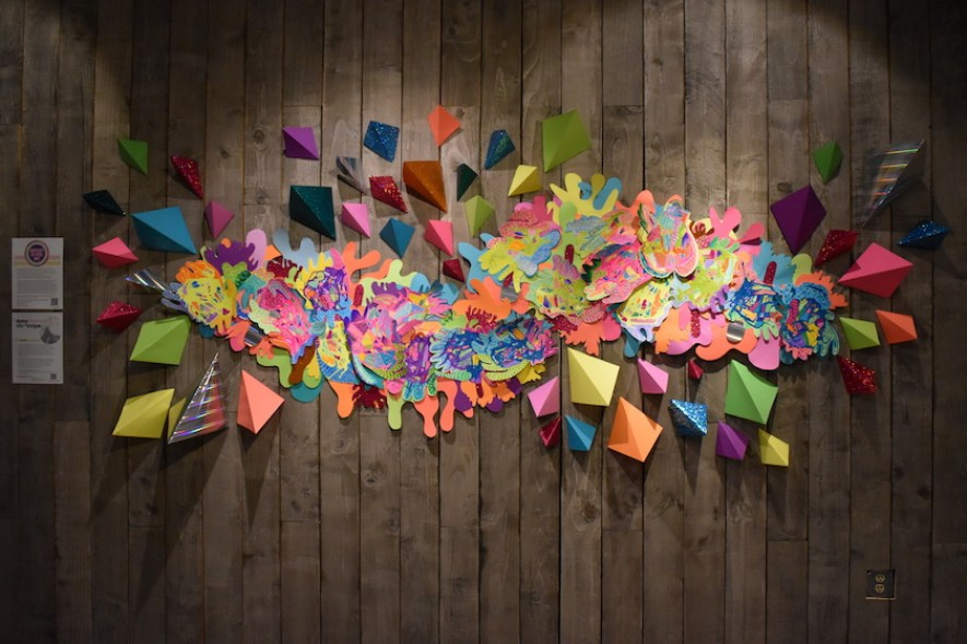 A multicolored art installation on a wood wall.