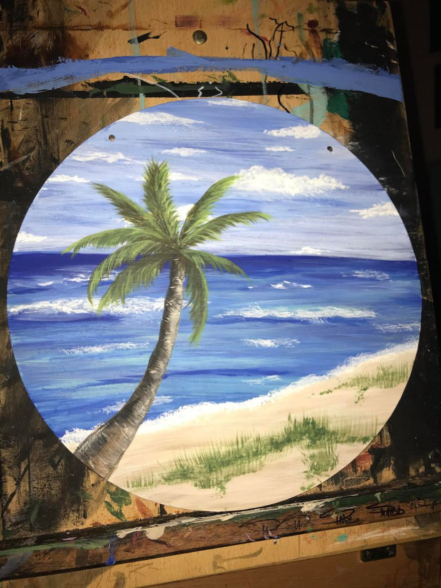 An art piece painted with a palm tree on a beach