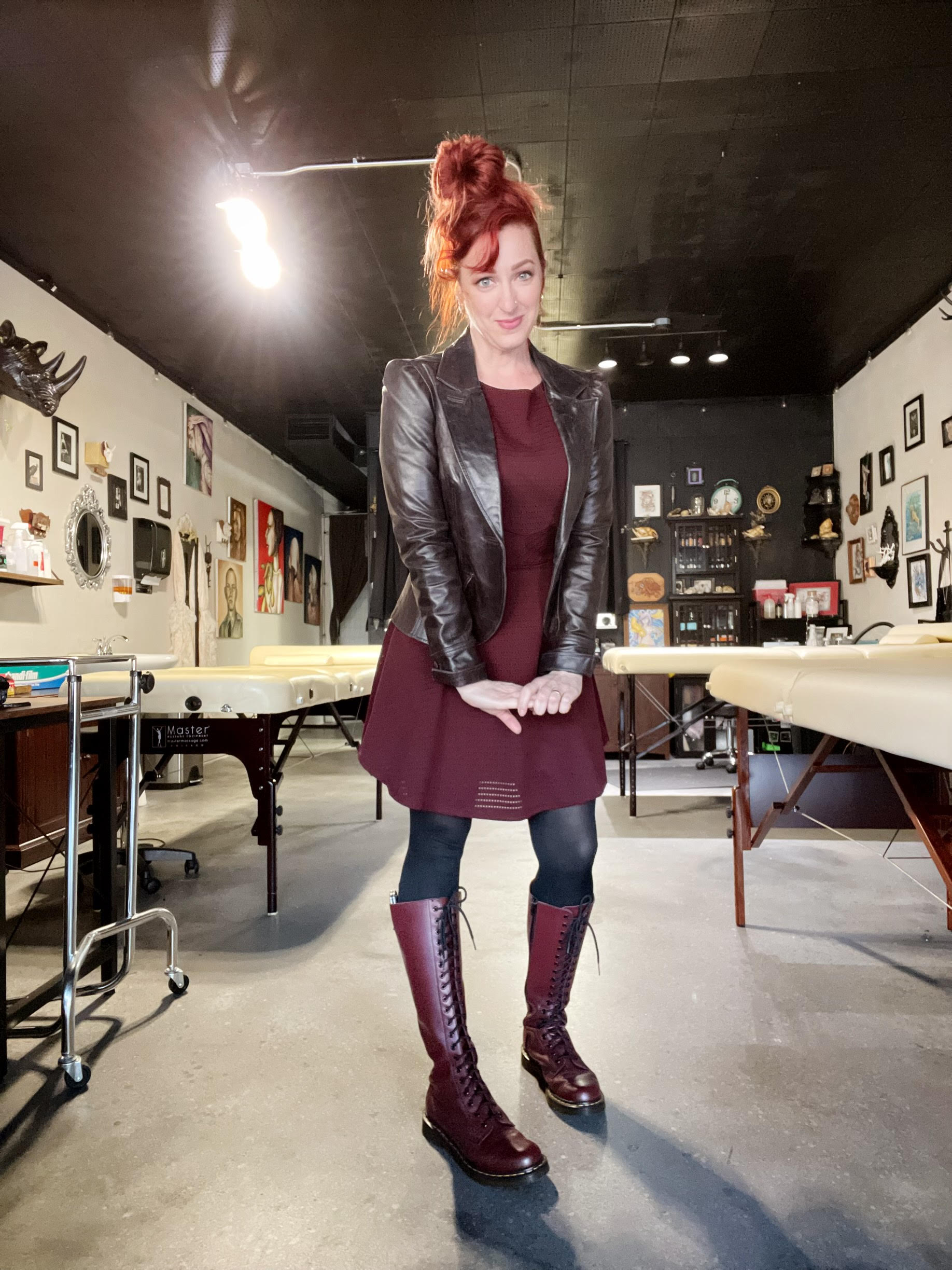 A photo of a woman with red hair and a leather jacket standing in an art studio