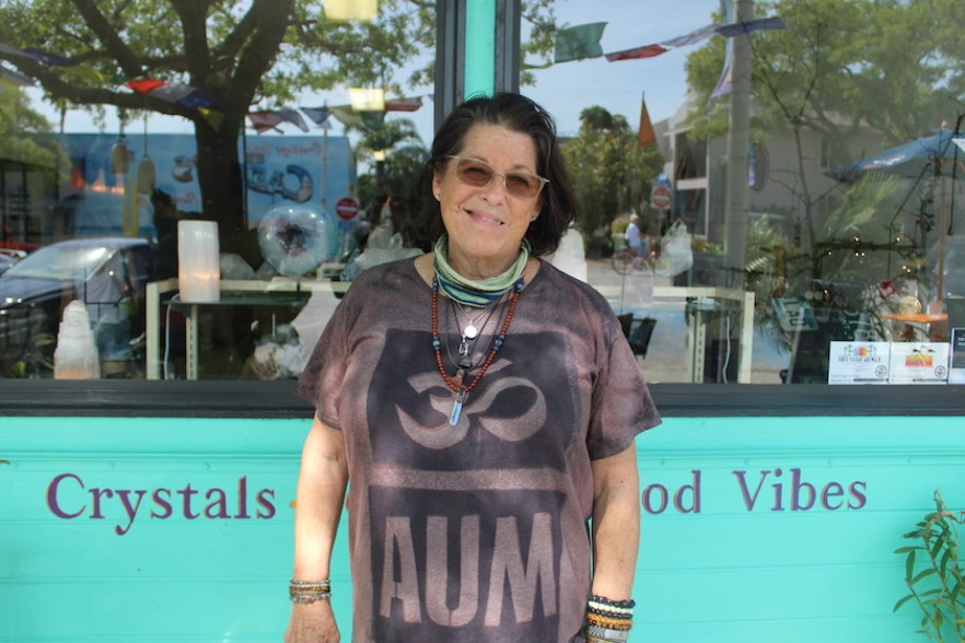 """A woman in a purple shirt and sunglasses attending in front of a shopfront painted blue that reads """"Crystals, Good Vibes"""""""