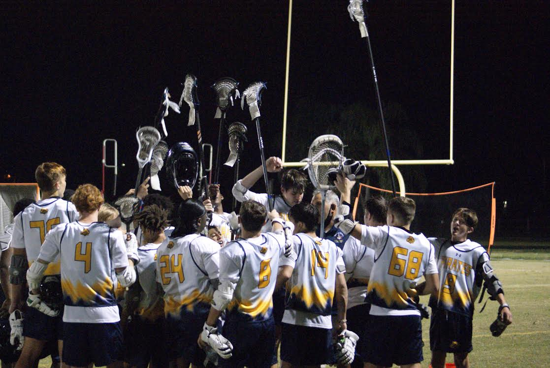 A group of lacrosse players in uniform on the field