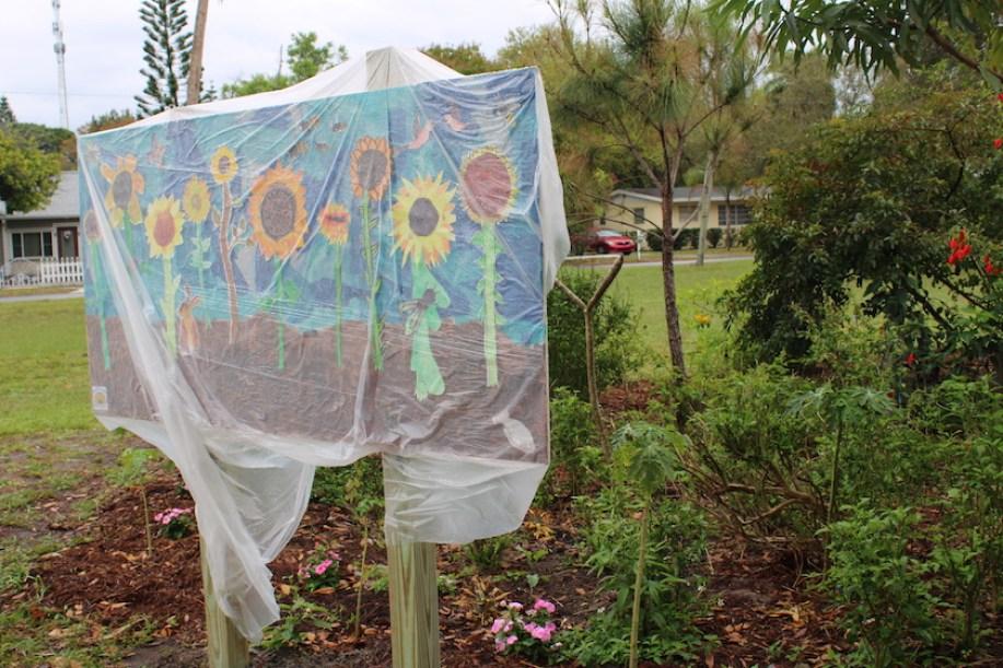 A painting under a sheer sheet outdoors in a garden.
