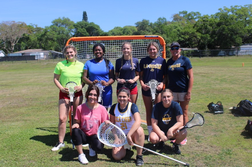 A group of lacrosse players on the field in front of the goal