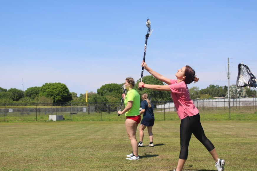 A girl in lacrosse uniform and stick on a field with other players