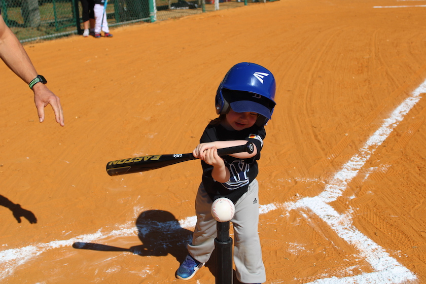 A little kid in a baseball outfit swinging a bat