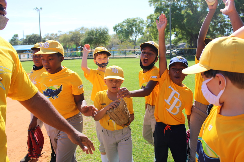 Kids in yellow baseball uniforms celebrating