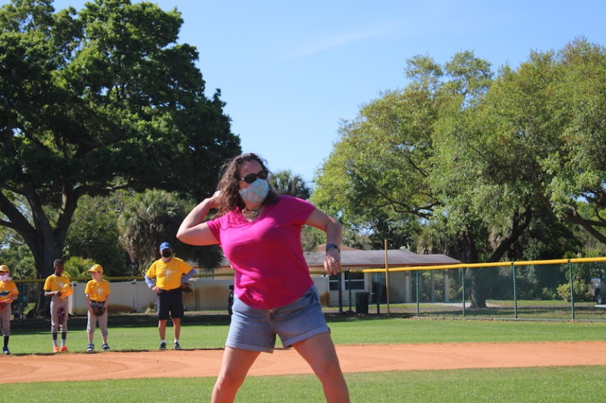 A woman in a pink shirt and face mask throwing a ball on a baseball field