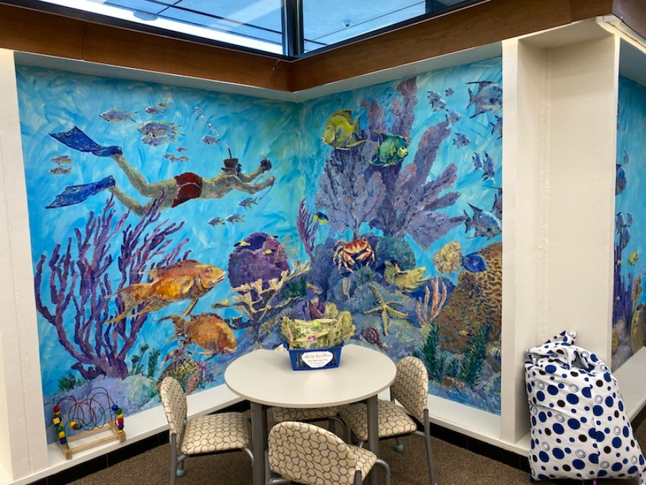An underwater mural painted in the corner of a room with a table and chairs