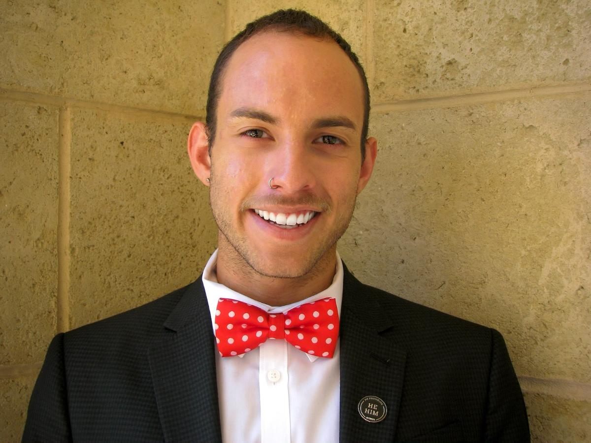 A head shot of a young man with a nose ring and a red bowtie