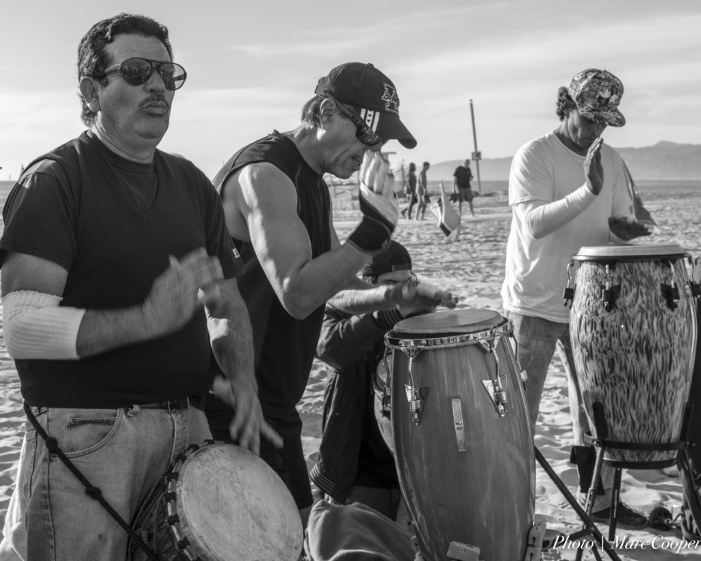 People on a beach drumming in black and white.